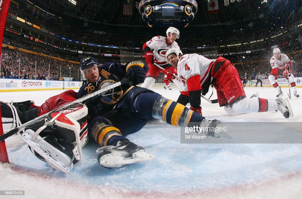 <a gi-track='captionPersonalityLinkClicked' href=/galleries/search?phrase=Thomas+Vanek&family=editorial&specificpeople=570606 ng-click='$event.stopPropagation()'>Thomas Vanek</a> #26 of the Buffalo Sabres crashes to the ice between goaltender <a gi-track='captionPersonalityLinkClicked' href=/galleries/search?phrase=Dan+Ellis&family=editorial&specificpeople=2235265 ng-click='$event.stopPropagation()'>Dan Ellis</a> #31 and Jamie McBain #4 of the Carolina Hurricanes on January 25, 2013 at the First Niagara Center in Buffalo, New York.