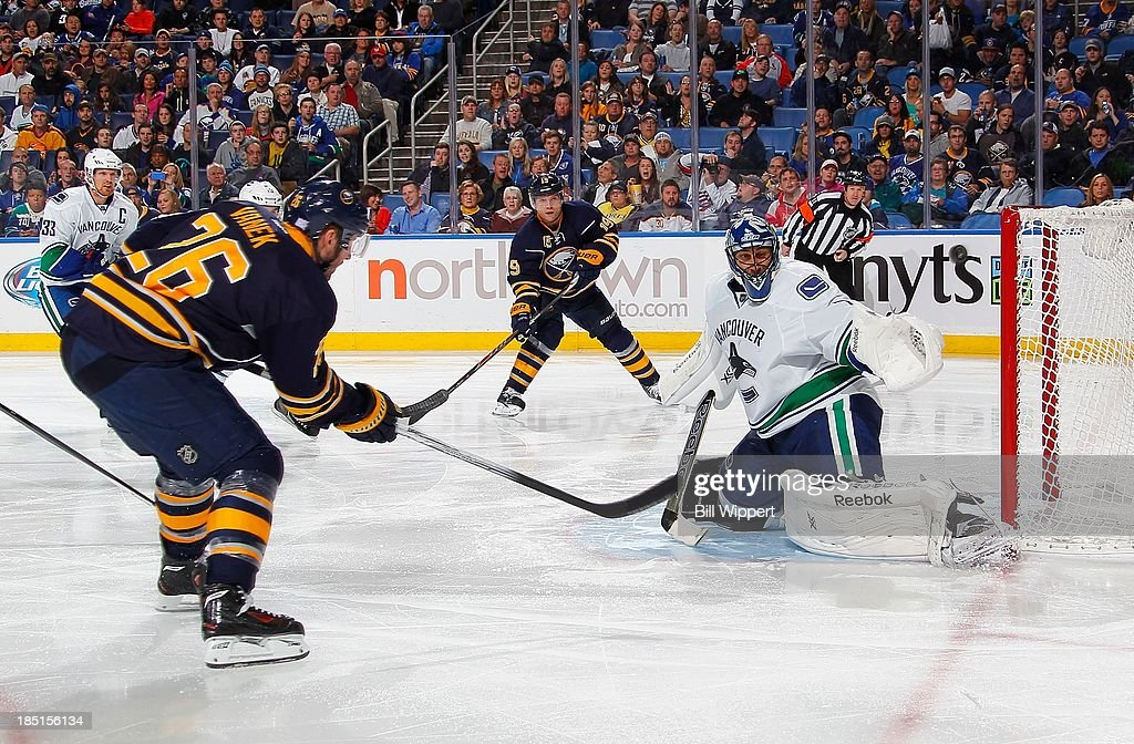 <a gi-track='captionPersonalityLinkClicked' href=/galleries/search?phrase=Thomas+Vanek&family=editorial&specificpeople=570606 ng-click='$event.stopPropagation()'>Thomas Vanek</a> #26 of the Buffalo Sabres fires the puck over the shoulder of <a gi-track='captionPersonalityLinkClicked' href=/galleries/search?phrase=Roberto+Luongo&family=editorial&specificpeople=202638 ng-click='$event.stopPropagation()'>Roberto Luongo</a> #1 of the Vancouver Canucks for an apparent third period goal that was disallowed after a video review on October 17, 2013 at the First Niagara Center in Buffalo, New York. Vancouver won, 3-0.
