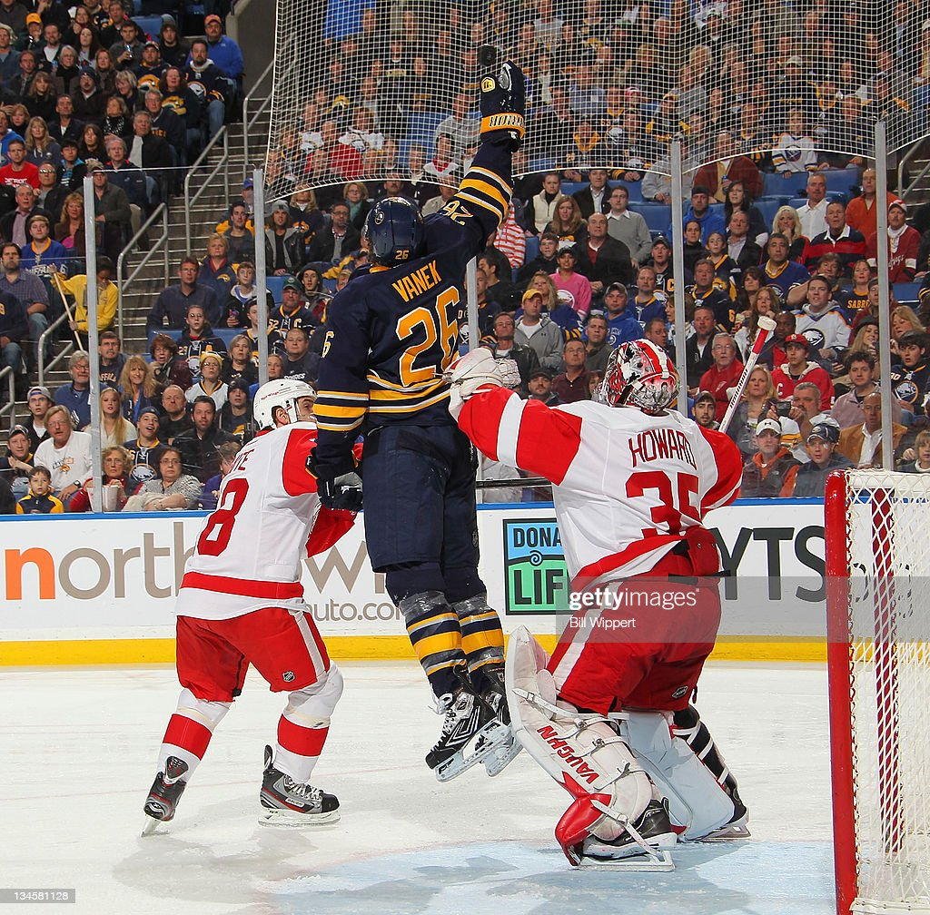 Thomas Vanek of the Buffalo Sabres jumps for a flying puck between Ian White and Jimmy Howard of the Detroit Red Wings at First Niagara Center on...