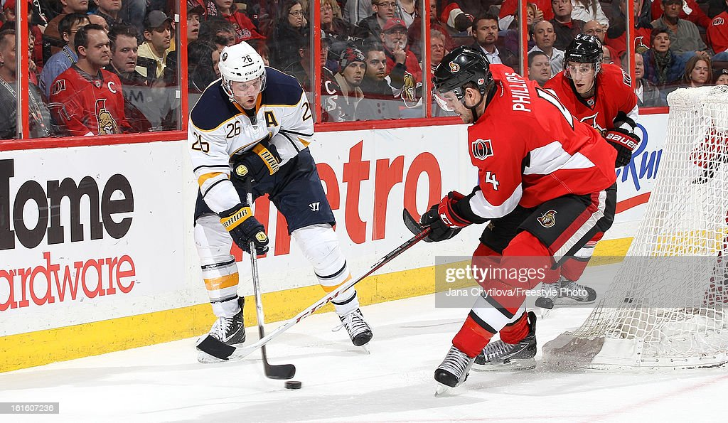 <a gi-track='captionPersonalityLinkClicked' href=/galleries/search?phrase=Thomas+Vanek&family=editorial&specificpeople=570606 ng-click='$event.stopPropagation()'>Thomas Vanek</a> #26 of the Buffalo Sabres shoots the puck past a defending Chris Phillips #4 of the Ottawa Senators, during an NHL game at Scotiabank Place on February 12, 2013 in Ottawa, Ontario, Canada.