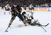 Thomas Vanek of the Buffalo Sabres tries to control the puck against Paul Martin and Zbynek Michalek of the Pittsburgh Penguins at HSBC Arena on...