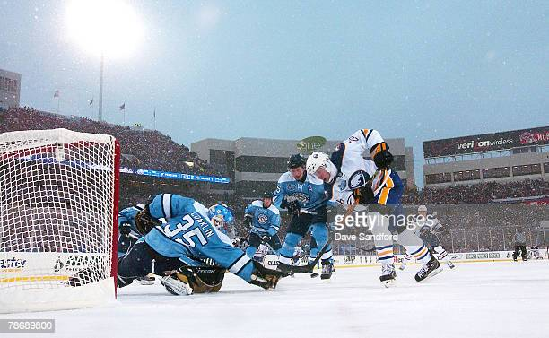 Thomas Vanek of the Buffalo Sabres tries to get past Darryl Sydor and goaltender Ty Conklin of the Pittsburgh Penguins during the NHL Winter Classic...