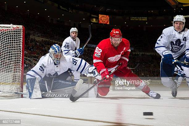 Thomas Vanek of the Detroit Red Wings battles for the puck with Matt Hunwick of the Toronto Maple Leafs in front of goaltender Frederik Andersen of...