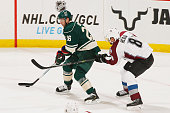 Thomas Vanek of the Minnesota Wild skates with the puck while Jan Hejda of the Colorado Avalanche defends during the season opener on October 9 2014...