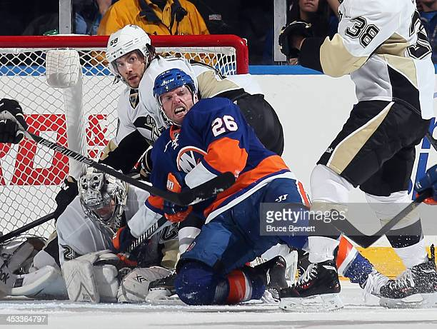 Thomas Vanek of the New York Islanders is knocked down in front of the Pittsburgh Penguins net during the third period at the Nassau Veterans...