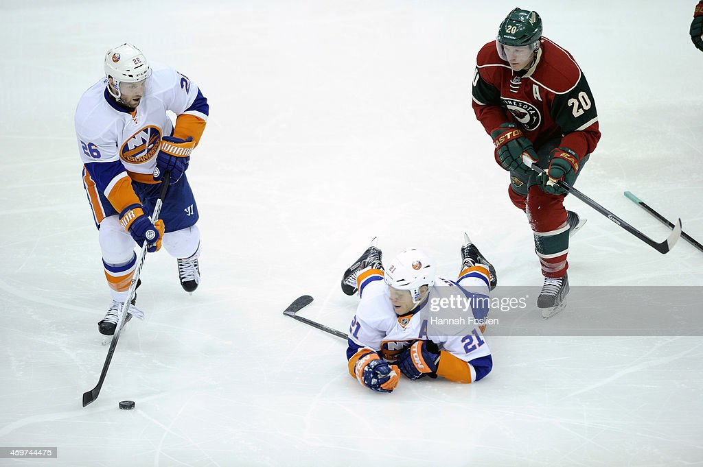 Thomas Vanek #26 of the New York Islanders takes the puck from teammate Kyle Okposo #21 as Ryan Suter #20 of the Minnesota Wild looks on during the third period of the game on December 29, 2013 at Xcel Energy Center in St Paul, Minnesota. The Islanders defeated 5-4.