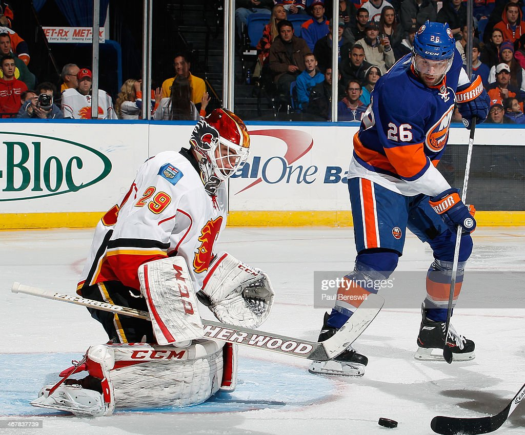 Thomas Vanek of the New York Islanders waits for a rebound as goalie Reto Berra of the Calgary Flames makes a save during an NHL hockey game at...
