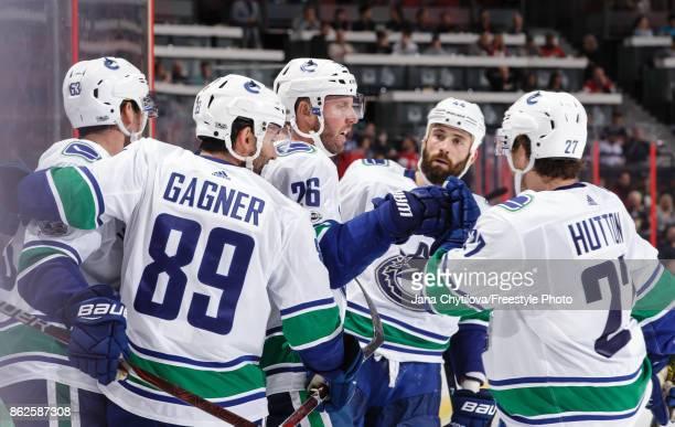 Thomas Vanek of the Vancouver Canucks celebrates his third period goal and 700th career NHL point against the Ottawa Senators with team mates Sam...