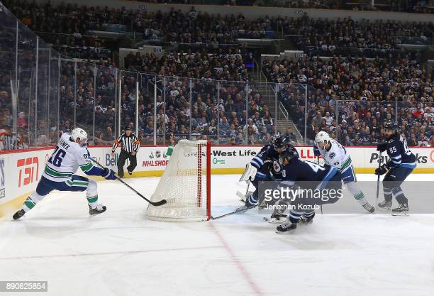 Thomas Vanek of the Vancouver Canucks centers the puck to teammate Michael Chaput as Ben Chiarot and Joel Armia of the Winnipeg Jets defends the...