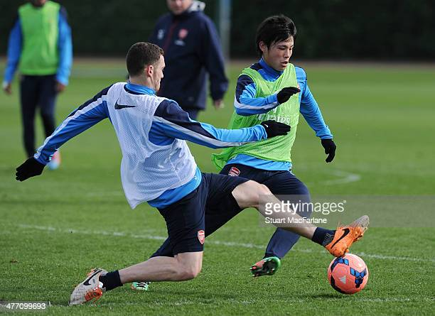 Thomas Vermaelen and Ryo Miyaichi of Arsenal during a training session at London Colney on March 7 2014 in St Albans England
