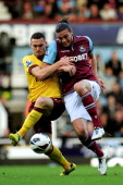 Thomas Vermaelen of Arsenal and Andy Carroll of West Ham compete for the ball during the Barclays Premier League match between West Ham United and...