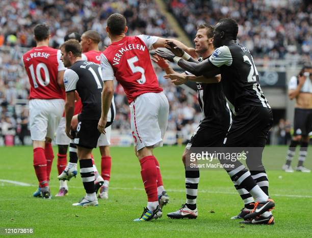 Thomas Vermaelen of Arsenal is pushed by Yohan Cabaye and Cheik Tiote of Newcastle after Gervinho is sent off during the Barclays Premier League...
