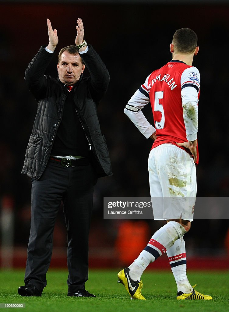 Thomas Vermaelen of Arsenal looks on as Manager Brendan Rogers of Liverpool applauds the fans at the final whistle during the Barclays Premier League match between Arsenal and Liverpool at Emirates Stadium on January 30, 2013 in London, England.