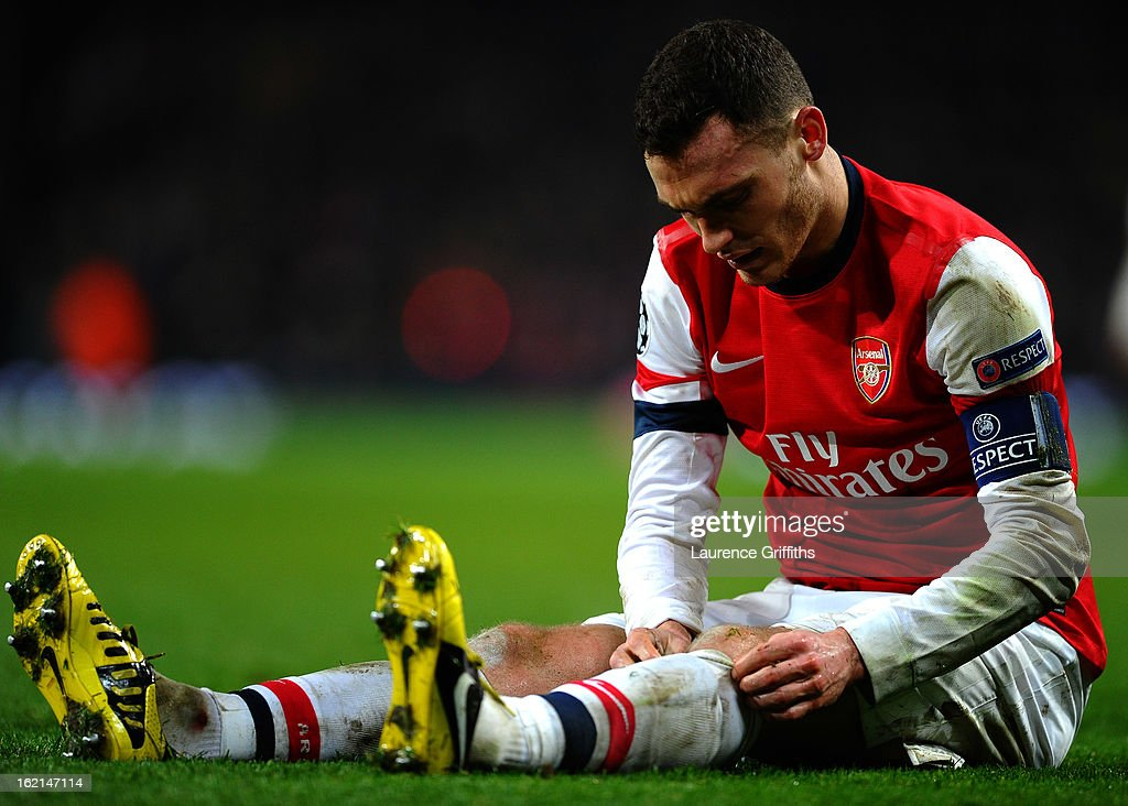 Thomas Vermaelen of Arsenal rolls his socks up as he sits on the turf during the UEFA Champions League round of 16 first leg match between Arsenal and Bayern Muenchen at Emirates Stadium on February 19, 2013 in London, England.