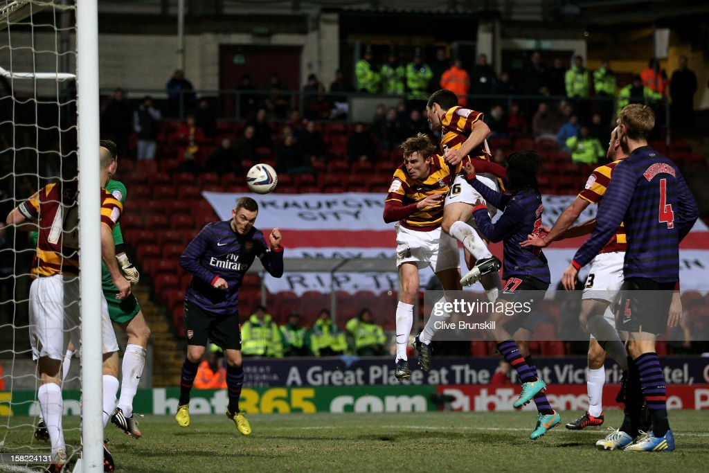 Thomas Vermaelen of Arsenal scores a goal with a header to level the scores at 1-1 during the Capital One Cup quarter final match between Bradford City and Arsenal at the Coral Windows Stadium, Valley Parade on December 11, 2012 in Bradford, England.