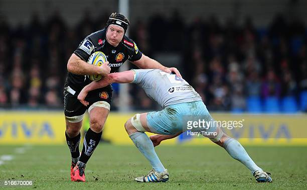 Thomas Waldrom of Exeter Chiefs is tackled by Christian Day of Northampton Saints during the Aviva Premiership match between Exeter Chiefs and...