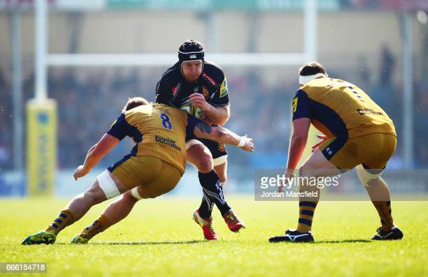Thomas Waldrom of Exeter is tackled by Ross Harrison and Mitch Eadie of Bristol during the Aviva Premiership match between Exeter Chiefs and Bristol...