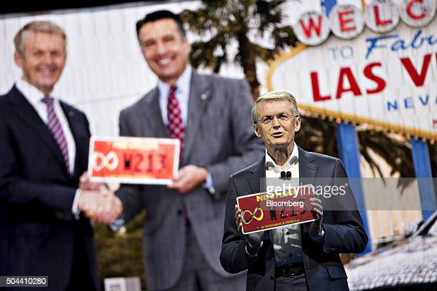Thomas Weber head of group research and MercedesBenz cars development at Daimler AG holds the license plate for a Mercedes autonomous vehicle during...