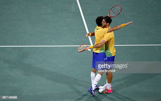Thomaz Bellucci and Andre Sa of Brazil celebrate victory against Andy Murray and Jamie Murray of Great Britain in the mens doubles on Day 2 of the...