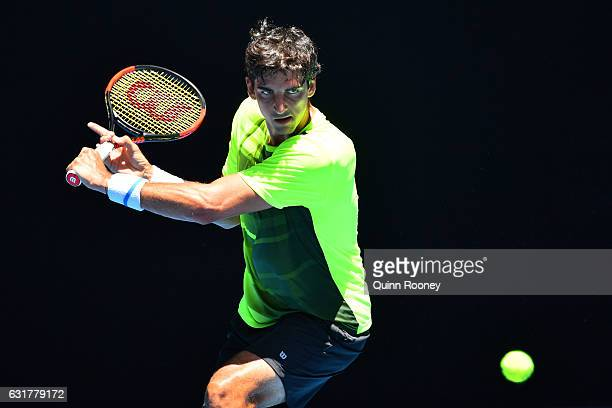 Thomaz Bellucci of Brazi plays a backhand in his first round match against Bernard Tomic of Australia on day one of the 2017 Australian Open at...
