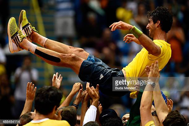 Thomaz Bellucci of Brazil is carried by teammates after winning his playoff singles match against Roberto Bautista Agut of Spain on the World Group...