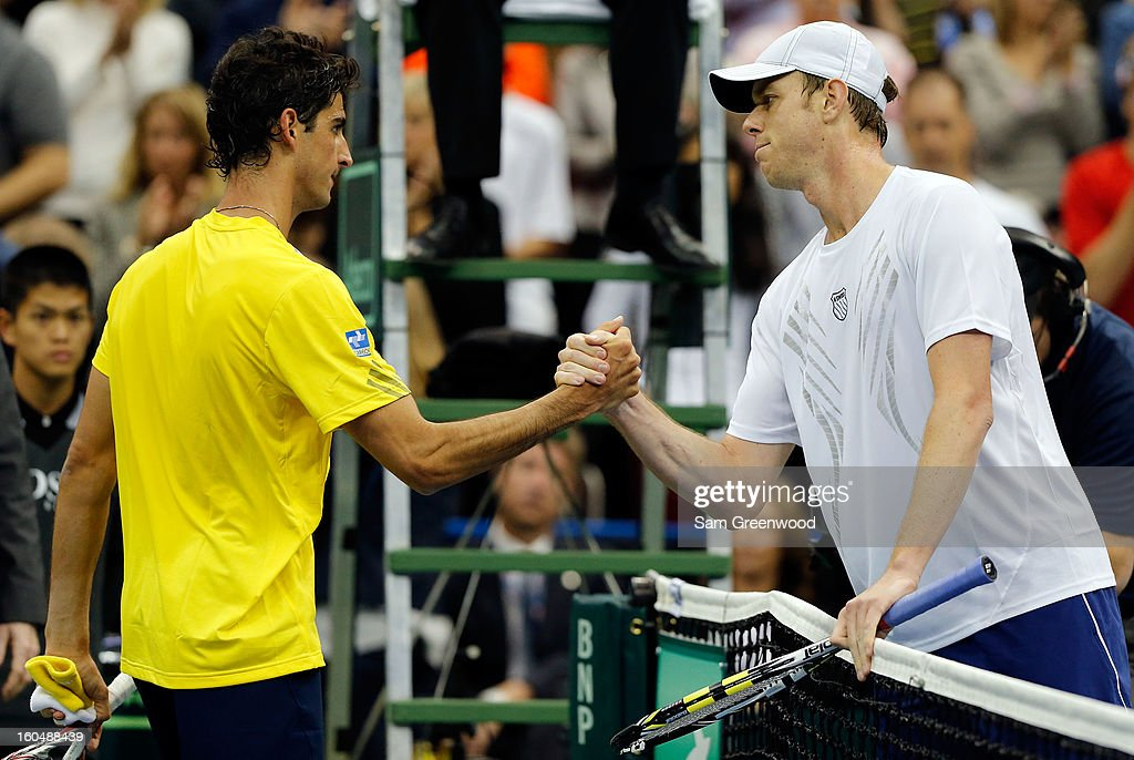 Thomaz Bellucci (L) of Brazil shakes hands with Sam Querrey of the United States following their singles match during the Davis Cup first round between the U.S. and Brazil at Veterans Memorial Arena on February 1, 2013 in Jacksonville, Florida.