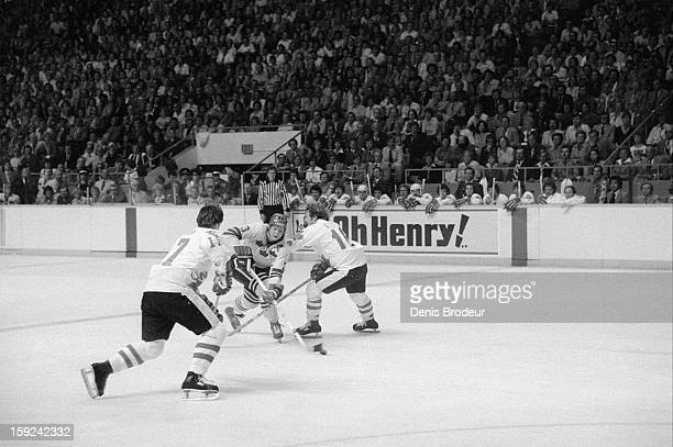 Thommie Bergman of team Sweden skates with the puck in between Bill Barber and Bobby Clarke of team Canada during a Canada Cup game at the Maple...