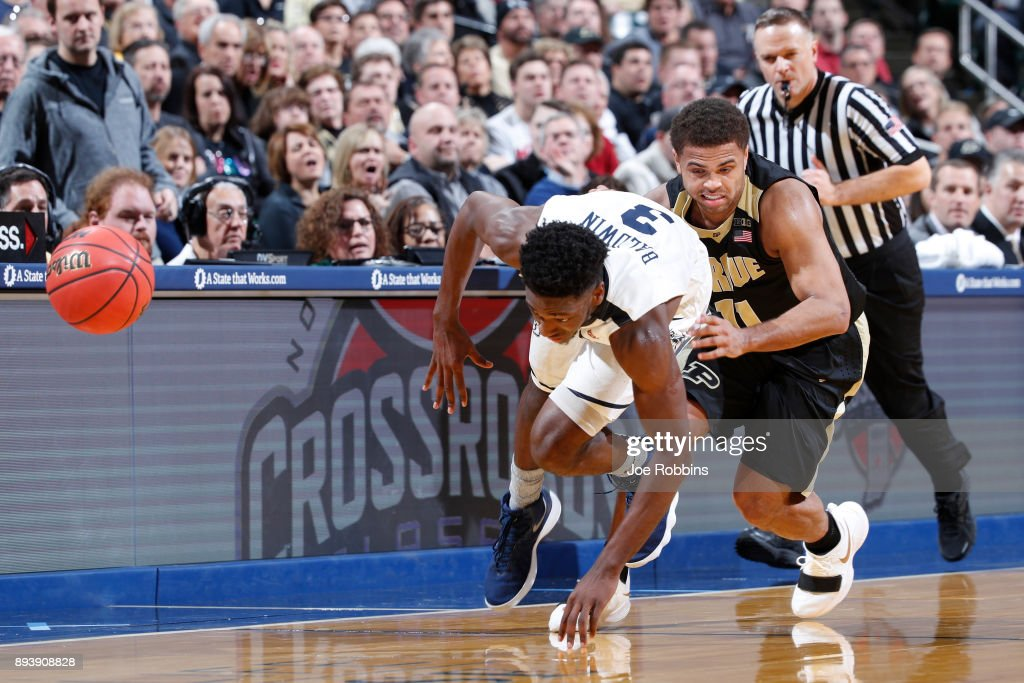 P.J. Thompson #11 of the Purdue Boilermakers fights for a loose ball against Kamar Baldwin #3 of the Butler Bulldogs in the second half of the Crossroads Classic at Bankers Life Fieldhouse on December 16, 2017 in Indianapolis, Indiana. Purdue won 82-67.