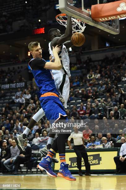 Thon Maker of the Milwaukee Bucks dunks in front of Kristaps Porzingis of the New York Knicks during the first half of a game at the BMO Harris...