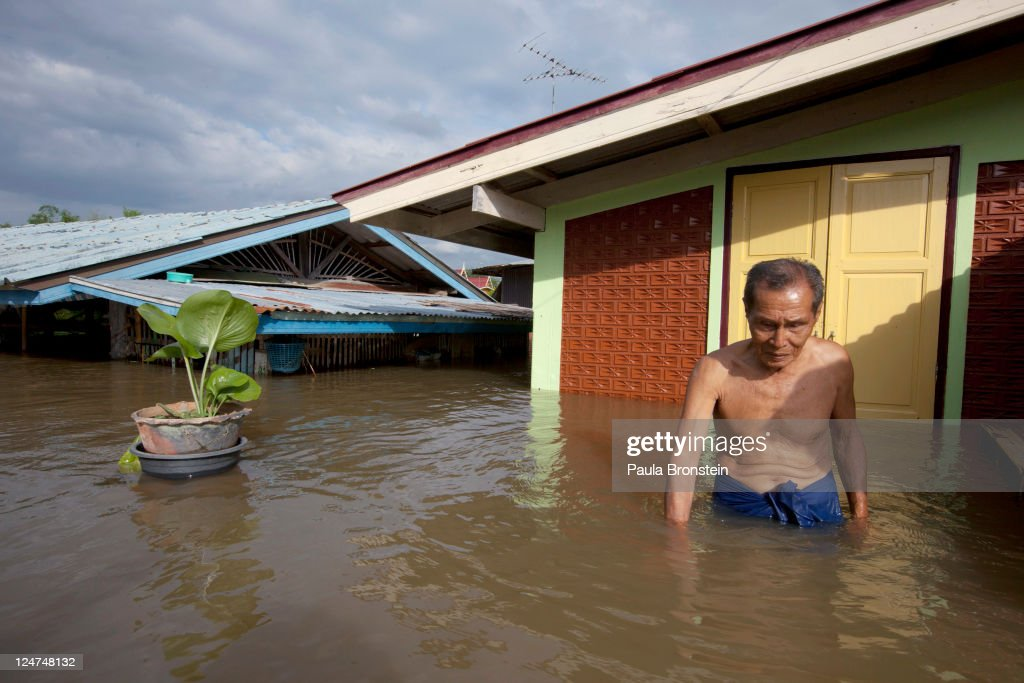 Thongbai Posuwan, 78, wades in the waters outside his flooded home September 12, 2011 Angthong, Thailand. Floods continue to ravage areas further south, with five people dying after a two-story apartment building sunk when a foundation collapsed due to rain and hillside runoff. The death toll continues to rise as 19 provinces remain affected by the annual rains.