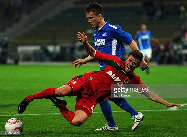 Thorben Stadler of Karlsruhe challenges Daniel Baier of Augsburg during the Second Bundesliga match between Karlsruher SC and FC Augsburg at Wildpark...
