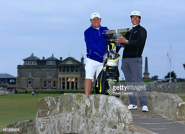 Thorbjorn Olesen of Denmark holds the trophy aloft with his caddie on the Swilcan Bridge on the 18th hole after victory in the 2015 Alfred Dunhill...
