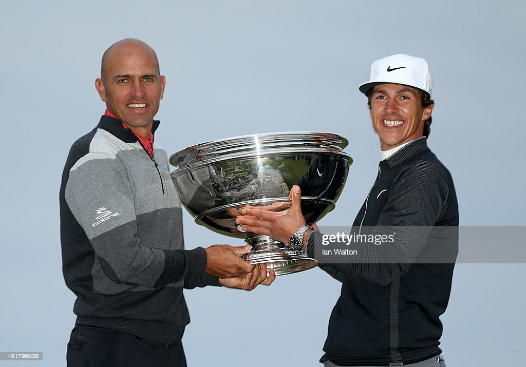 Thorbjorn Olesen of Denmark holds the trophy aloft with his playing partner American surfing champion Kelly Slater on the Swilcan Bridge on the 18th...