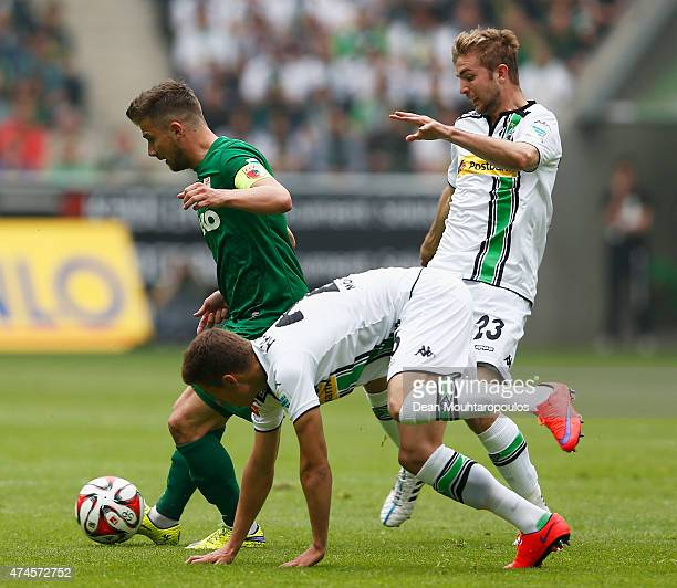 Thorgan Hazard and Christoph Kramer of Borussia Moenchengladbach chase Daniel Baier of FC Augsburg during the Bundesliga match between Borussia...