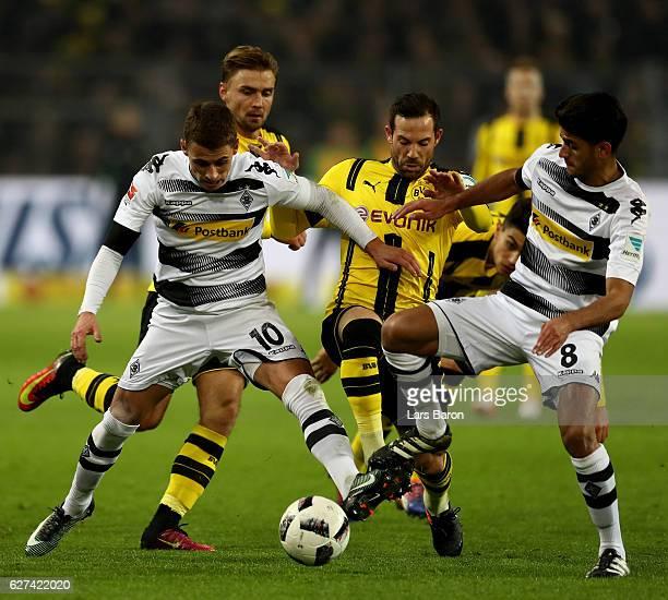 Thorgan Hazard of Borussia Moenchengladbach and Mahmoud Dahoud of Borussia Moenchengladbach challenge Gonzalo Castro of Borussia Dortmund during the...