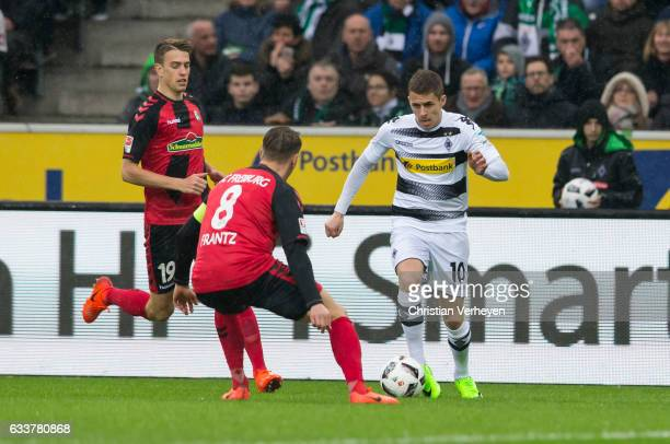 Thorgan Hazard of Borussia Moenchengladbach battle for the ball Mike Frantz and Janik Haberer of SC Freiburg during the Bundesliga Match between...
