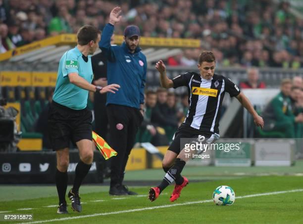 Thorgan Hazard of Borussia Moenchengladbach controls the ball and Head coach Sandro Schwarz of FSV Mainz 05 gestures during the Bundesliga match...