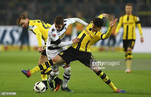 Thorgan Hazard of Borussia Moenchengladbach is challenged by Marcel Schmelzer and Marc Bartra of Dortmund during the Bundesliga match between...