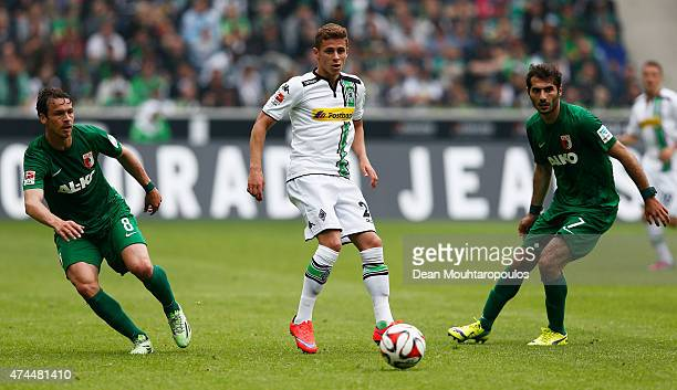 Thorgan Hazard of Borussia Moenchengladbach passes the ball between Halil Altintop and Markus Feulner of FC Augsburg during the Bundesliga match...