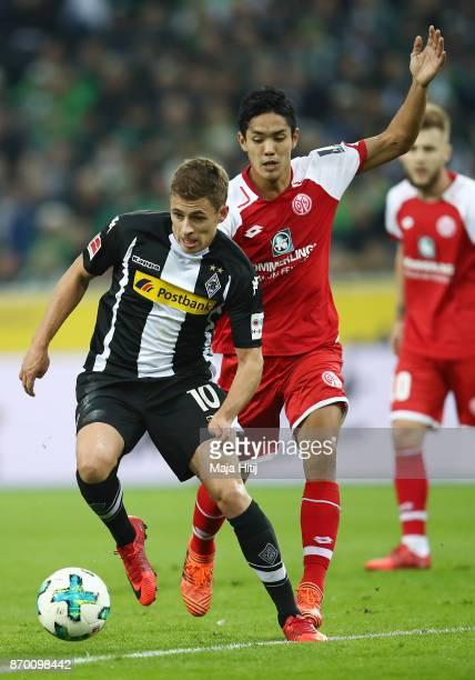 Thorgan Hazard of Moenchengladbach is chased by Yoshinori Muto of Mainz during the Bundesliga match between Borussia Moenchengladbach and 1 FSV Mainz...