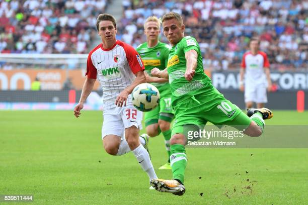 Thorgan Hazard of Moenchengladbach runs with the ball while Raphael Framberger of Augsburg looks on during the Bundesliga match between FC Augsburg...