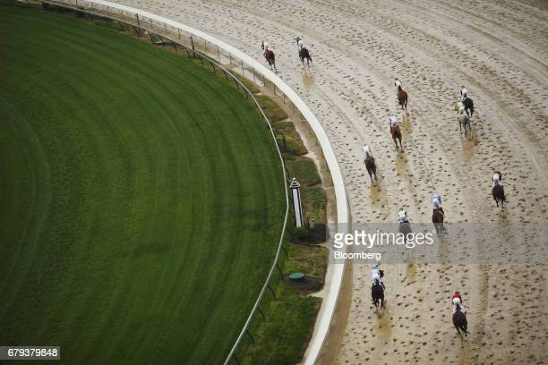 Thoroughbred racehorses round a turn after crossing the finish line during race on the eve of the Kentucky Derby at Churchill Downs in Louisville...