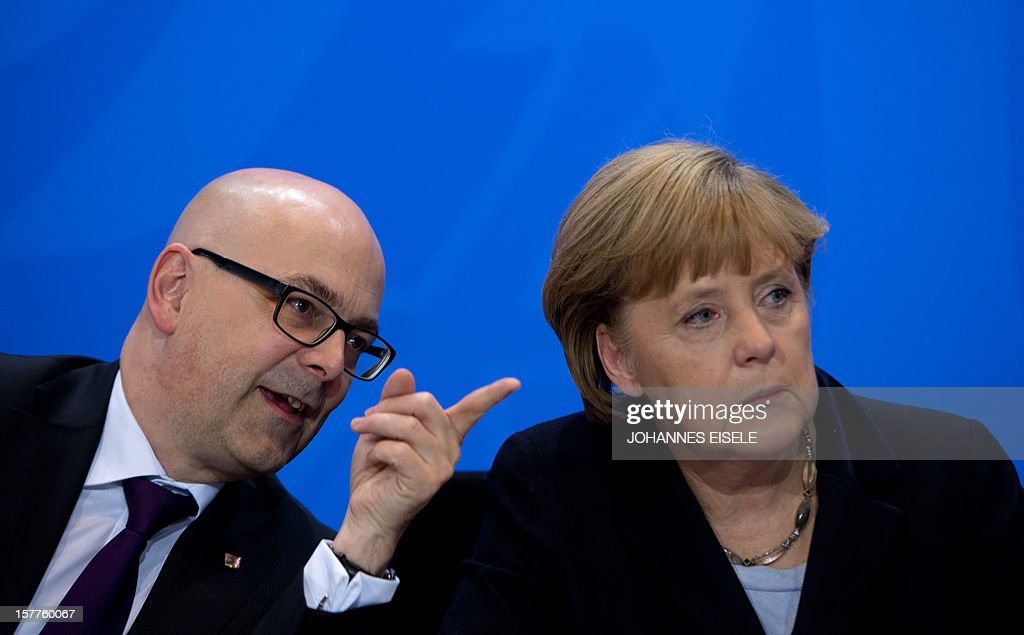 Thorsten Albig, Schleswig Holstein's State Premier and German Chancellor Angela Merkel address a press conference at the Chancellery in Berlin on December 6, 2012, after a meeting with heads of Germany's 16 regional states which is expected to decide whether to press ahead with launching a procedure aimed at banning the far-right NPD party a day after the Interior ministers from the regional states decided unanimously to launch a fresh bid to outlaw the neo-Nazi party, despite fears the effort could backfire. EISELE