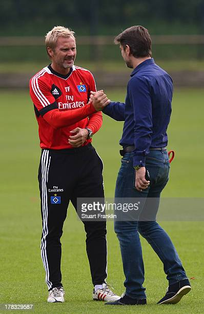 Thorsten Fink head coach of Hamburg greets Oliver Kreuzer sports director of Hamburg during the training session of Hamburger SV on August 29 2013 in...