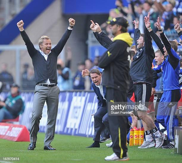 Thorsten Fink of Hamburg celebrates hius team's first win of the season as Juergen Klopp head coach of Dortmund looks on during the Bundesliga match...