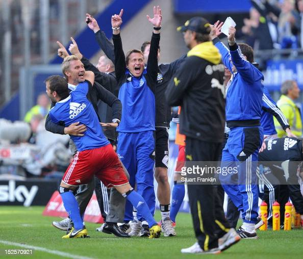 Thorsten Fink of Hamburg celebrates with Rafael Van Der Vaart as his team's first win of the season as Juergen Klopp head coach of Dortmund looks on...