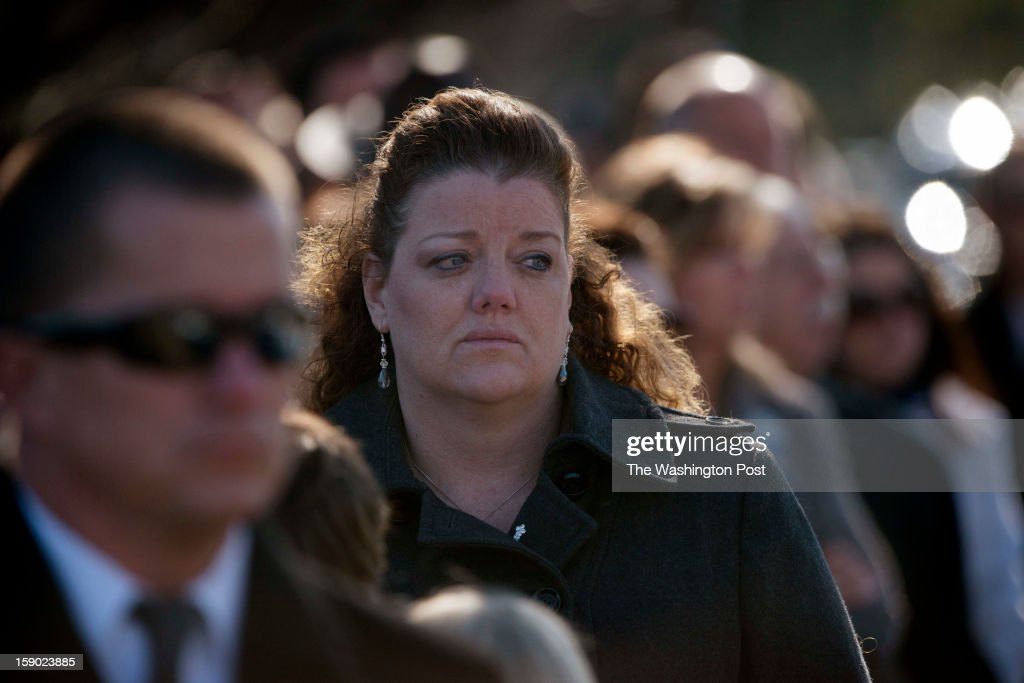 Those attending the funeral watch as the body of Prince William County Police Officer Chris Yung is carried out of Hylton Memorial Chapel in Woodbridge, VA on Friday, January 4, 2013.