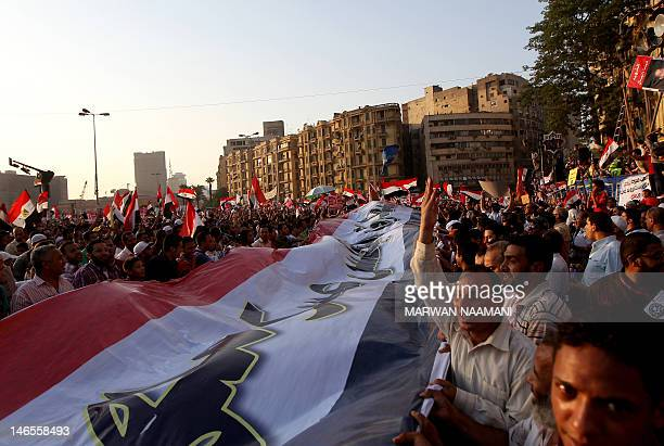 Thosuands of Egyptian supporters of the Mulsim Brotherhood presidential candiade Mohammed Mursi wave their national flag as they gather in Cairo's...