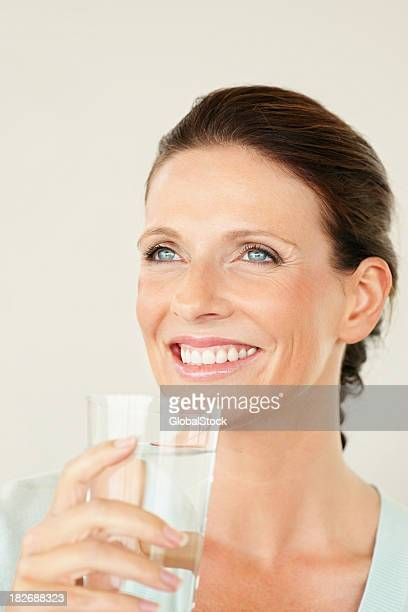 Thoughtful and smiling woman holding a glass of water