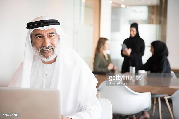 Thoughtful Arab businessman smiling in office